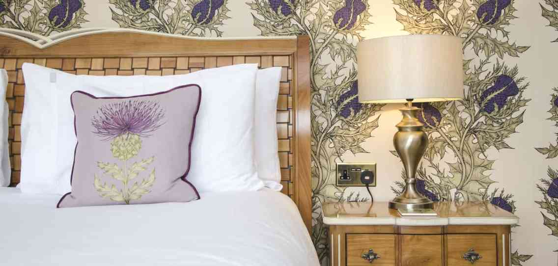 Hand painted thistle wallpaper from Timorous Beasties with a wooden headboard against it with white bedlinen and purple cushions
