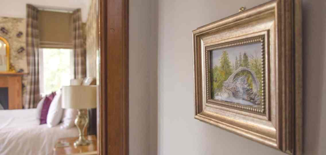 View into the Spey bedroom at Firhall B&B with a watercolour picture of the bridge at Carrbridge on the wall
