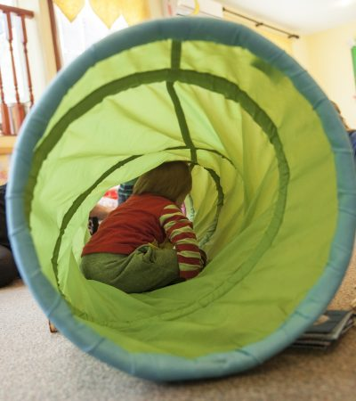 kid playing in toy tunnel