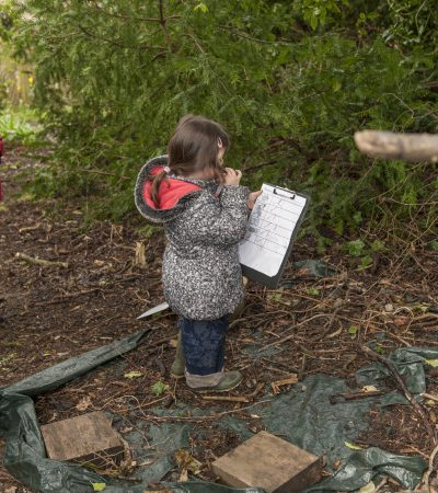 child standing with a clipboard