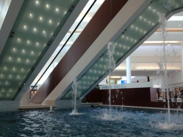 Escalator lines above a line of fountains