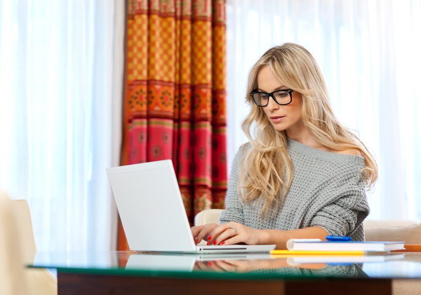 Female writer seated at desk and typing on laptop