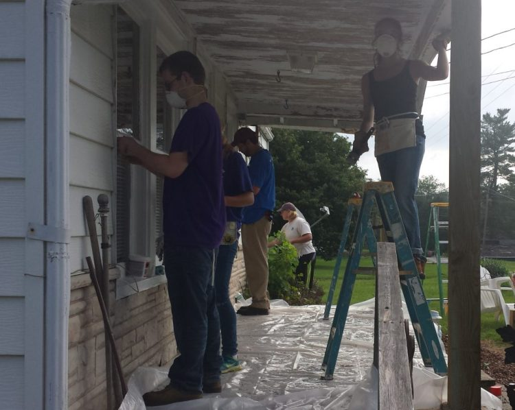 Youth repairing a home
