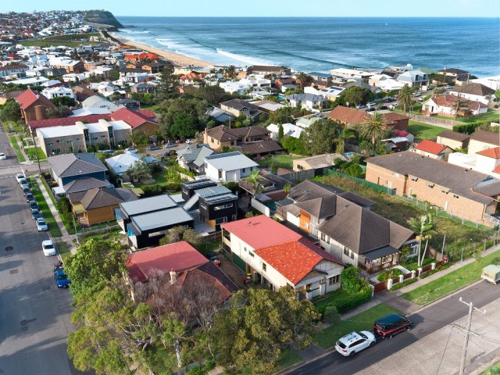 drone real estate photography showing homes in Newcastle NSW with beach in background