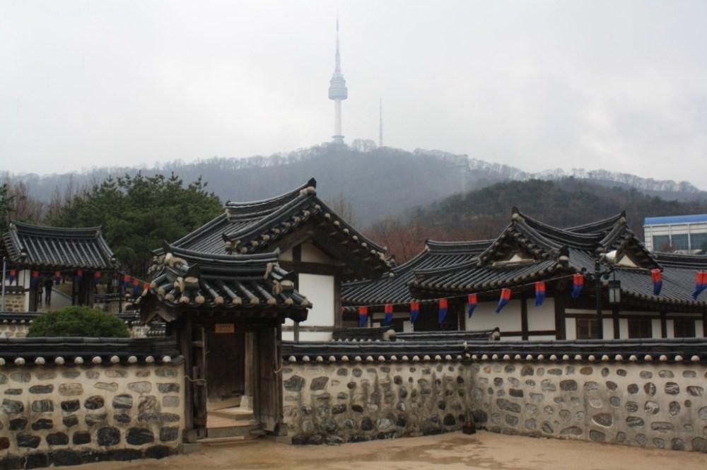 Traditional Korean folk houses. Behind is the N Seoul Tower.