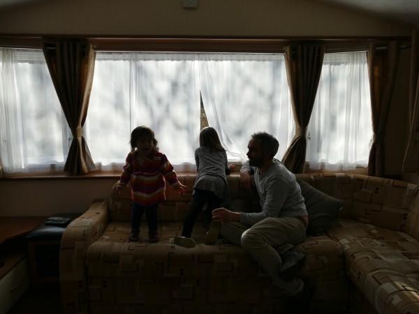 famille devant une fenêtre dans un mobil-home dans le Glen Coe