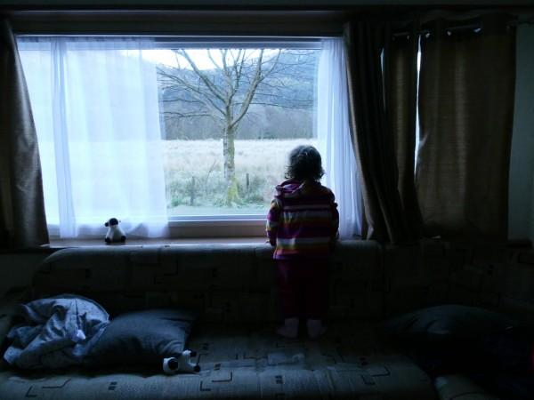 enfant devant une fenêtre dans un mobil-home dans le Glen Coe
