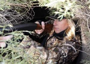 Jen Carroll from Celina, Texas, watches for birds while hunting ducks and geese from a pit blind in a rice field.