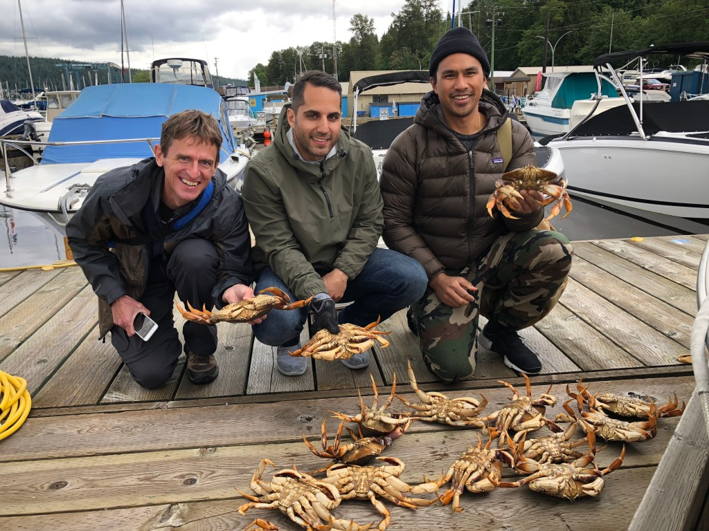 Three smiling anglers holding their daily catch of Crab