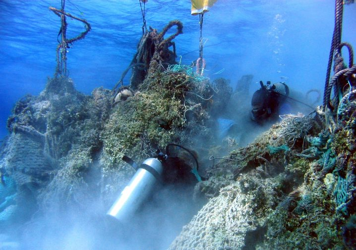 A SCUBA diver helping to free ghost nets from the sea floor so they can be lifted to the surface