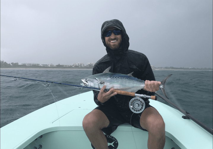 A smiling angler in a rain jacket and shorts holding a false albacore and a fly fishing rod on a boat.