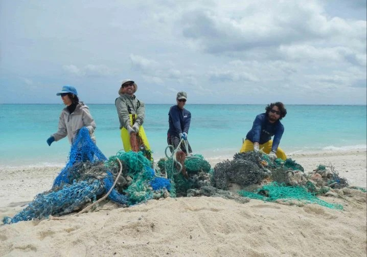 Four people standing on a beach with a pile of ghost fishing nets they removed from the sea
