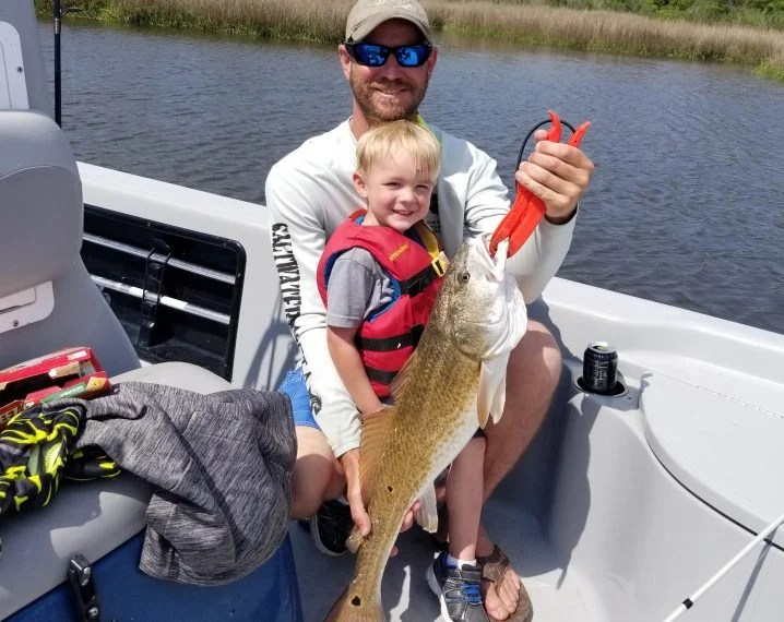 A child and father holding a Redfish on a boat