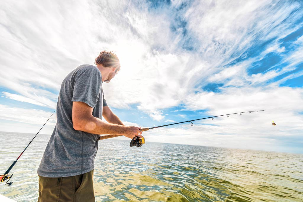 A man fishing in the shallow clear waters of the Everglades Park
