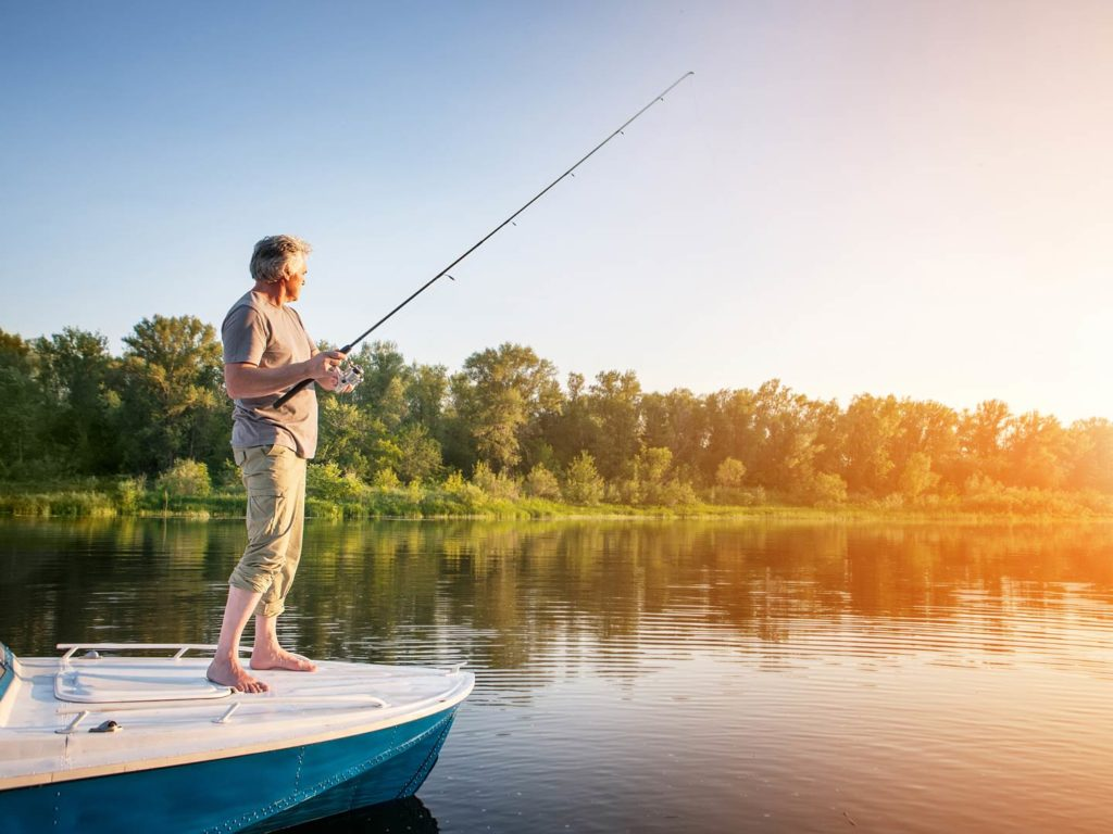 A mature man fishing from a boat