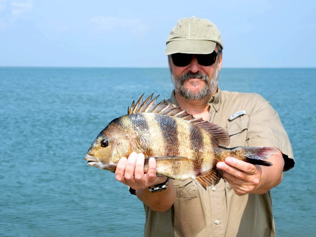 An angler holding a Sheepshead with water in the background