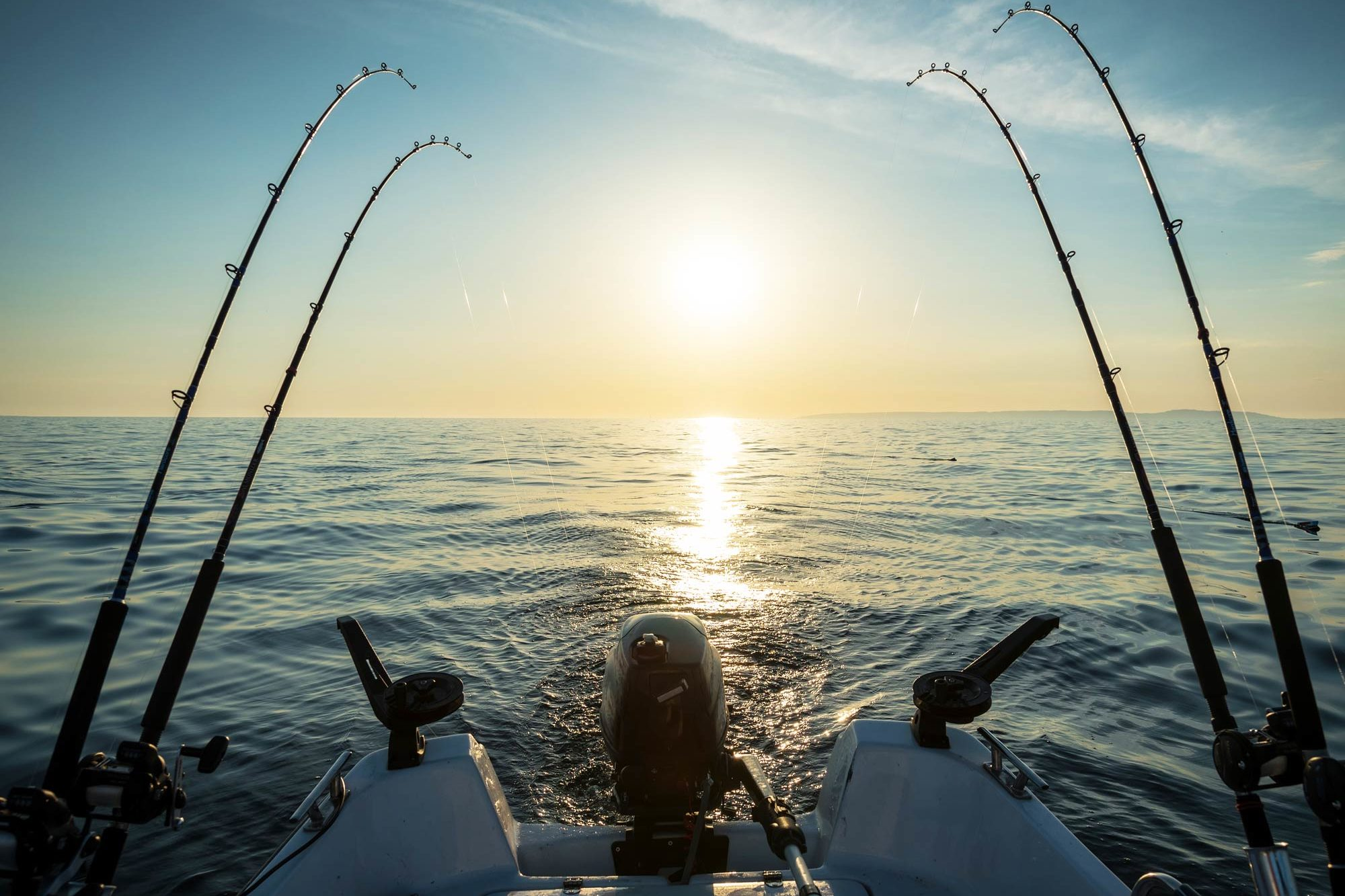 Four trolling fishing rods on a boat just after sunrise