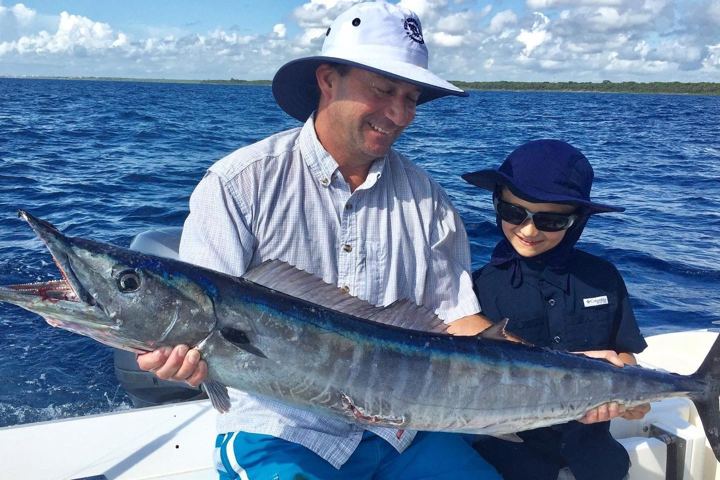 Father and son smiling and holding a giant Wahoo with water and skies as backdrop