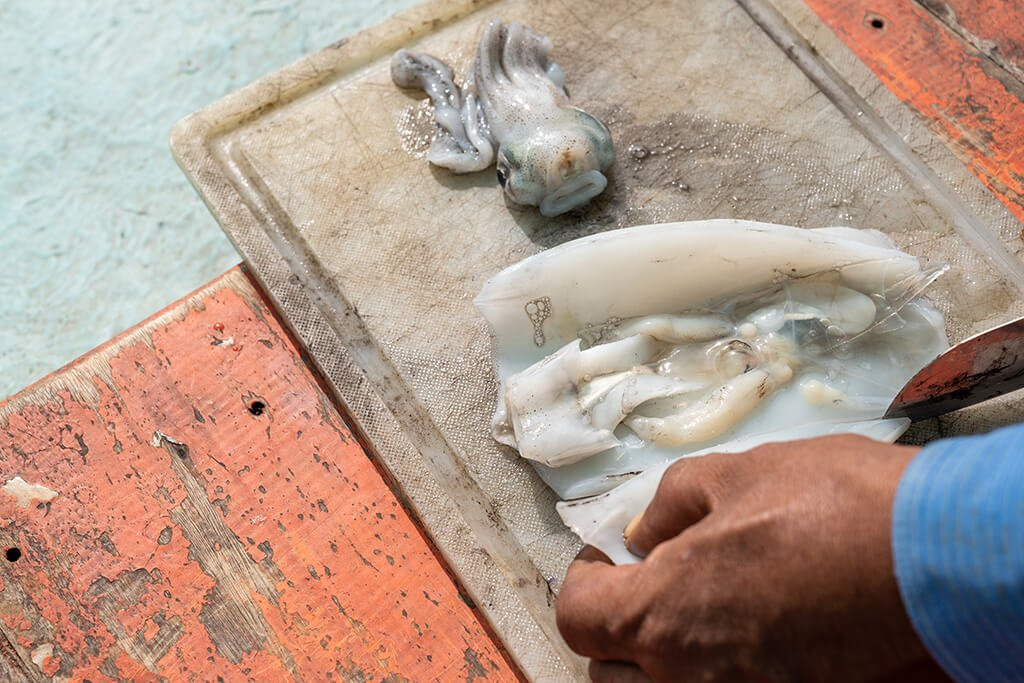 A man cutting up squid to use as bait