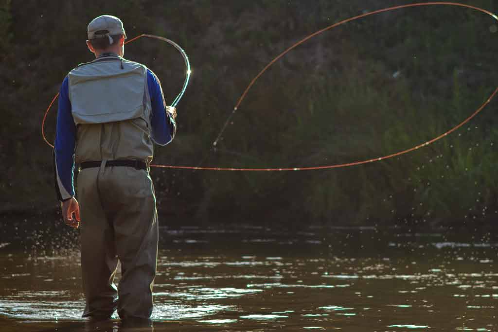 A man fly fishes for Salmon in a freshwater river with his back to the camera and his line out