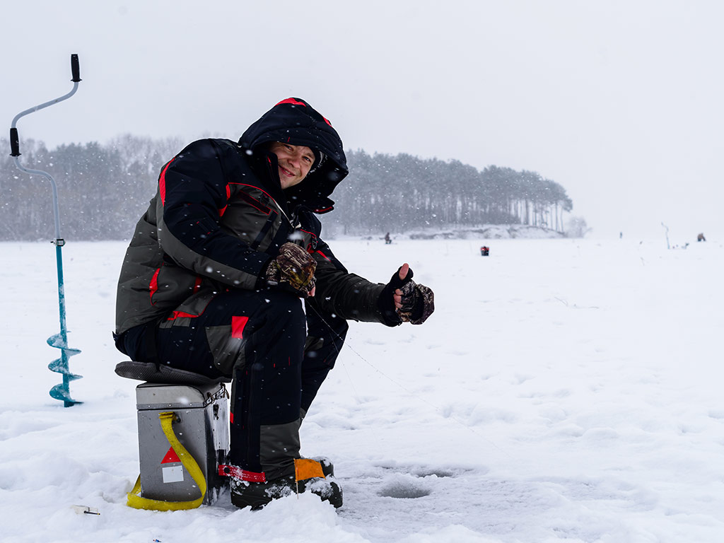 An angler sitting on a box and holding a thumbs up over a hole in the ice.
