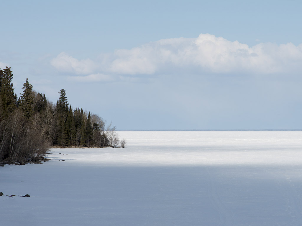 View of a frozen Lake Winnipeg with some trees to the left and clouds above.