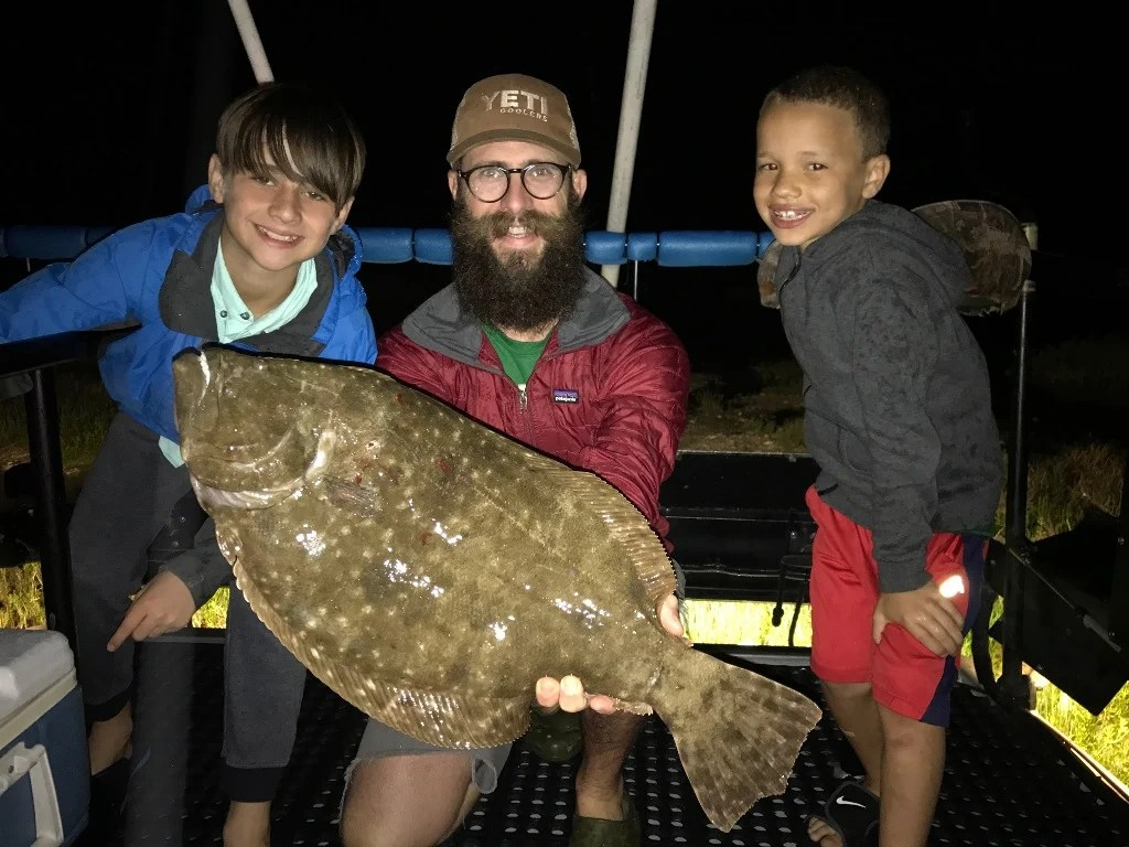 A happy angler with two kids on a boat holding a Flounder caught by gigging