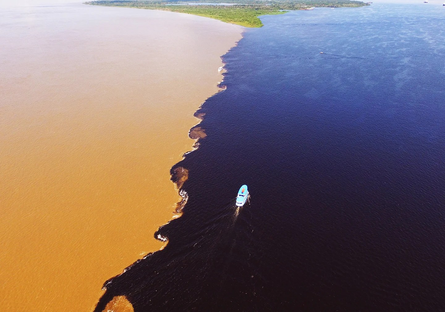 A boat on the Amazon River at the meeting of the Rio Negro and the Amazon