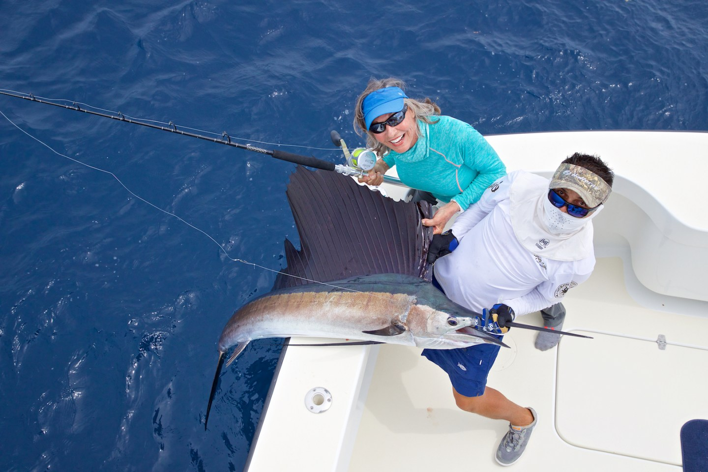 a bird's eye view of an angler and guide posing with a Sailfish they just caught