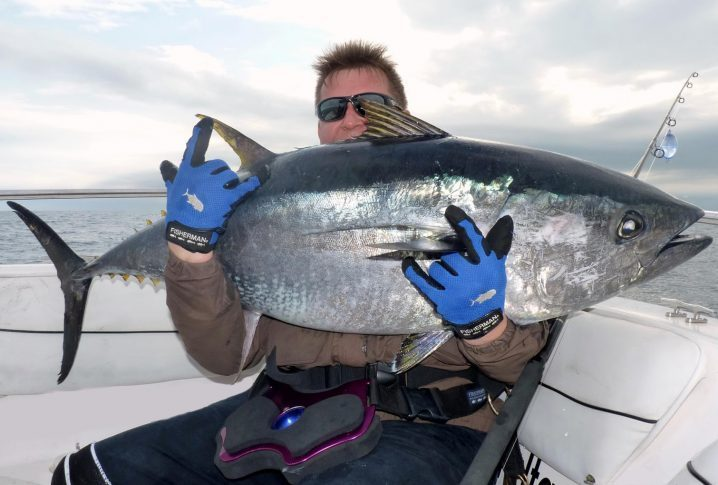 an angler holding a big Bluefin Tuna on a fishing boat