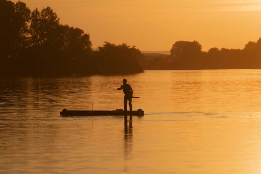 A man stands on a boat throwing bait into Sodenica Lake as dusk settles
