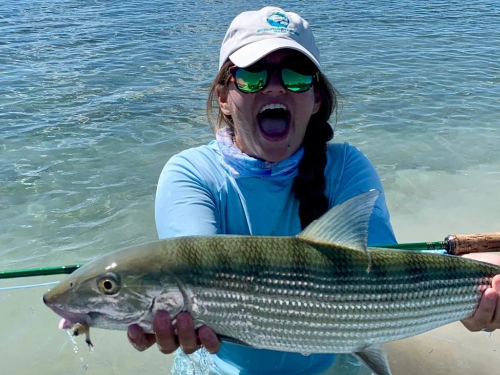 A laughing woman angler in a cap and sunglasses holding a Bonefish