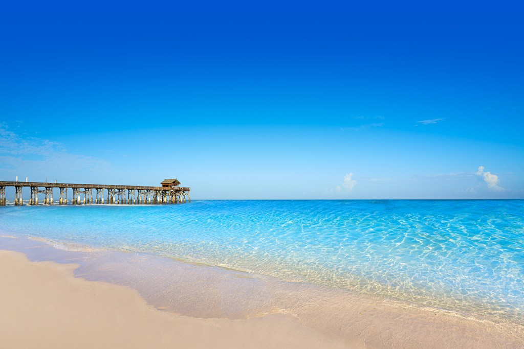 A sunny beach in Cape Canaveral, Florida. Yellow sand flows into bright blue water with an old fishing pier in the distance.