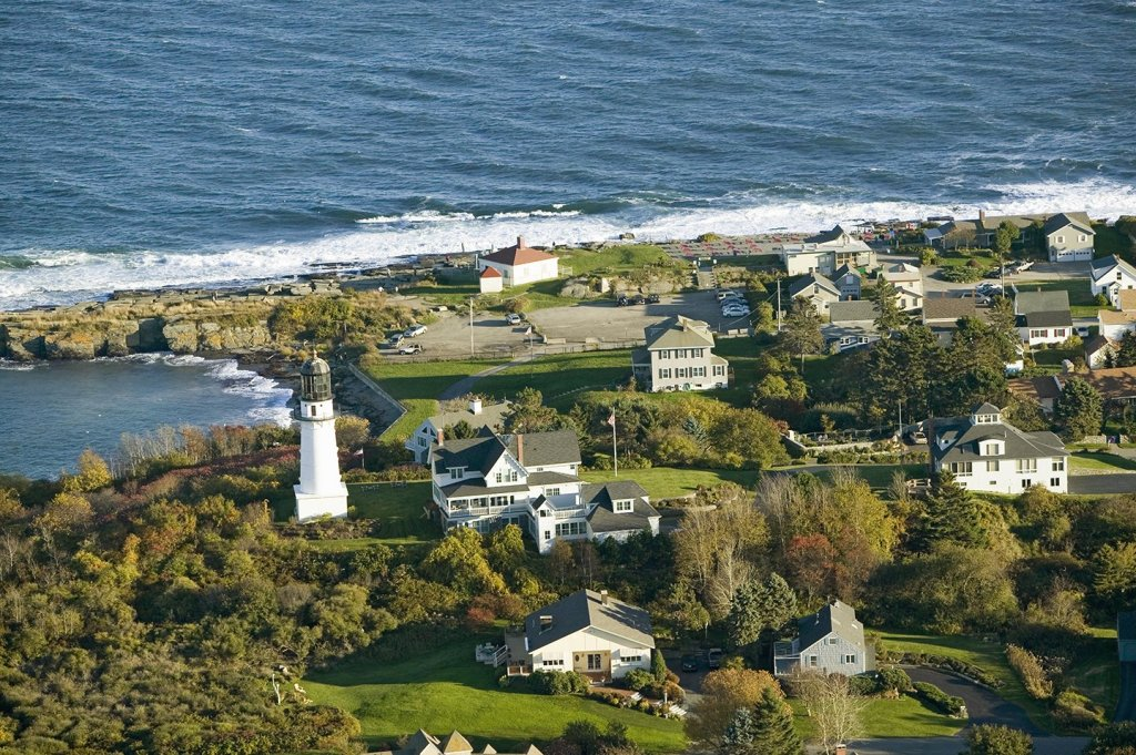 Houses and a lighthouse by the sea in Cape Elizabeth, one of the best coastal towns in Maine