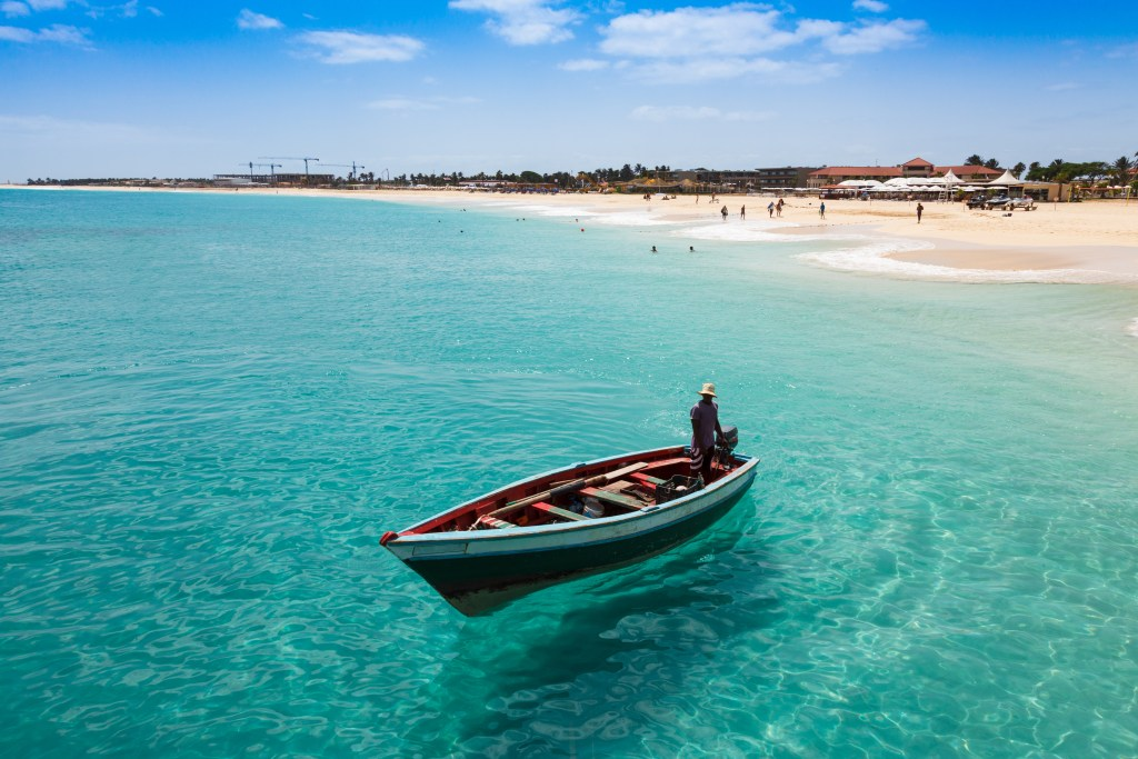Fisherman on a boat in turquoise water, white sand beach and people swimming behind him, Cape Verde Islands