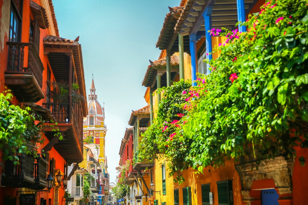 A street of colorful old Spanish colonial buildings in Cartagena, Colombia. Green plants hang off the balconies on the right, and a church is visible in the distance.