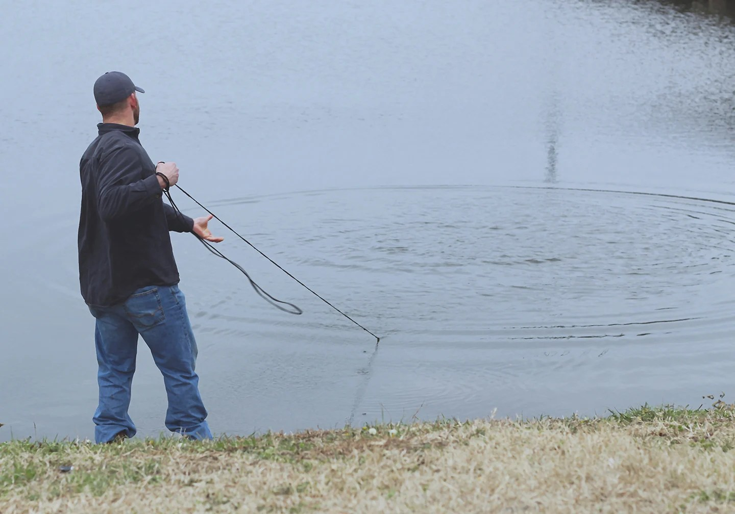 An angler standing by a lake pulling in a bait net on a catfishing trip
