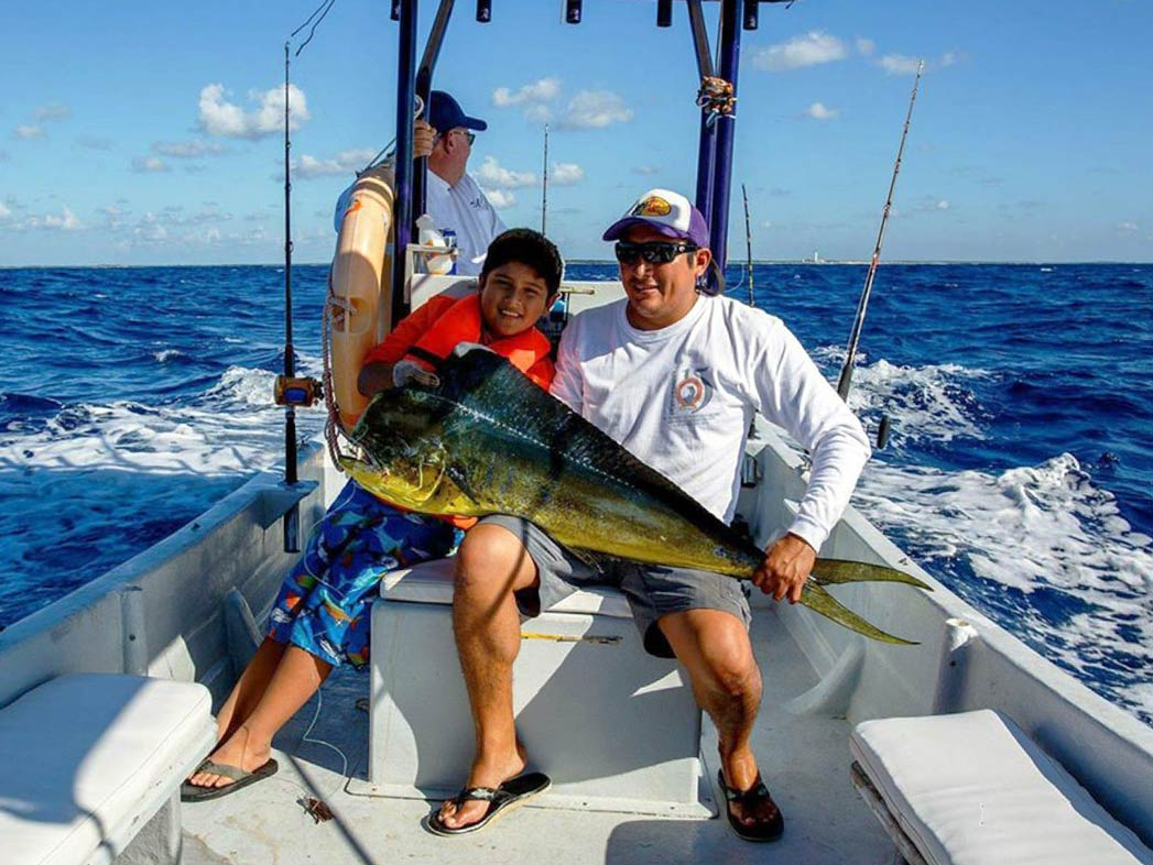 Two adults and a child sit on a sport fishing vessel holding a Mahi Mahi and smiling