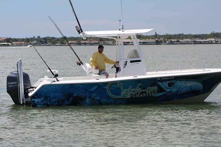 A charter captain standing on his boat on the water