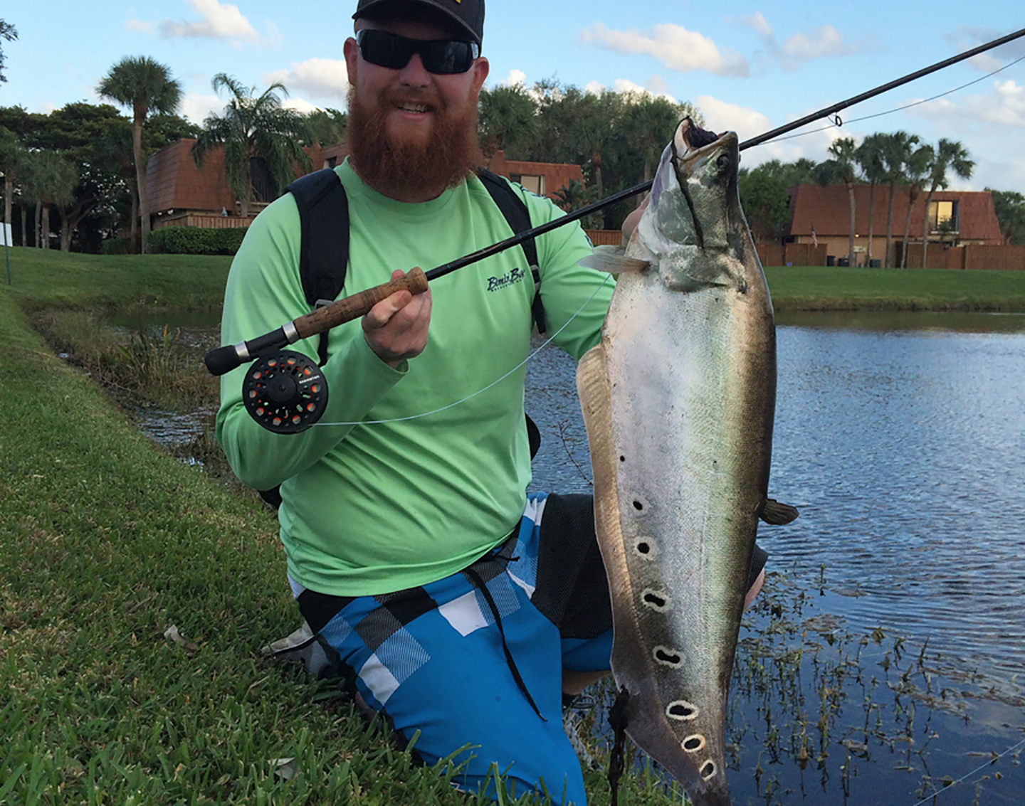 An anglers holding a fly fishing rod and an invasive clown knife fish.
