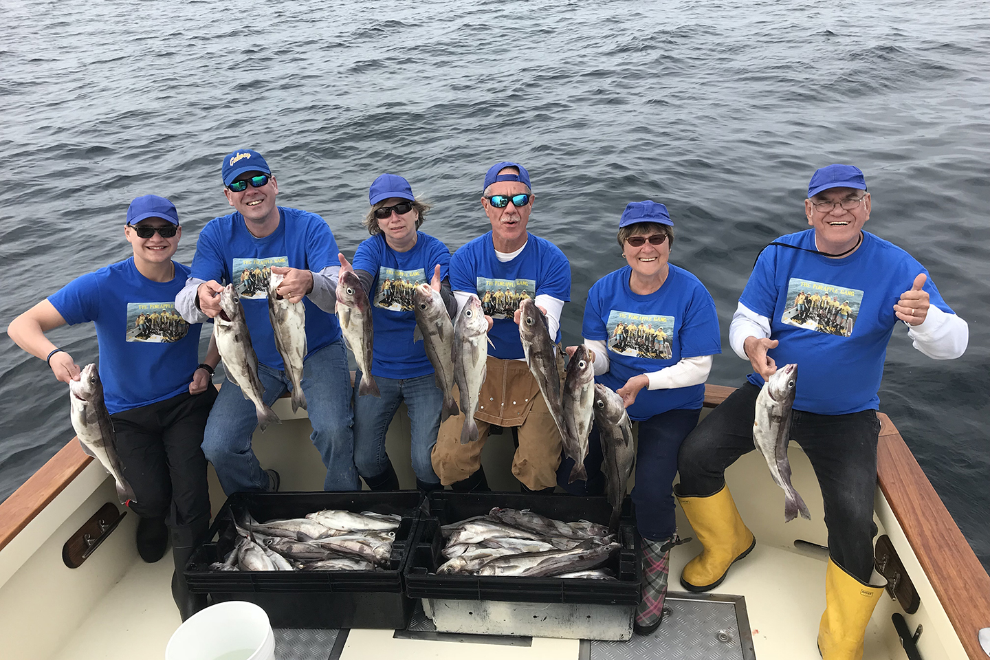A group of anglers dressed in blue shirts and caps. The anglers are sitting at the back of a charter boat holding up some Haddock that they have just caught
