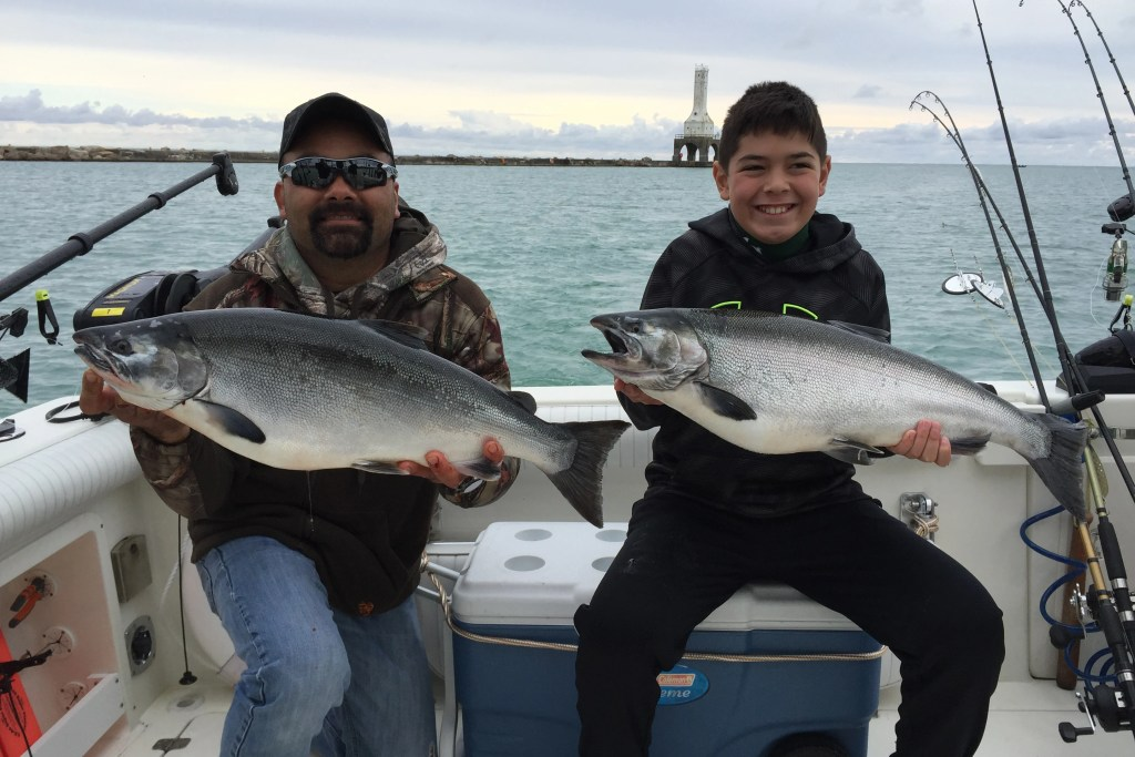 A man in a cap and sunglasses and a boy in a black sweater holding large Coho Salmon on a fishing charter. The sea is visible behind them, with land in the distance.