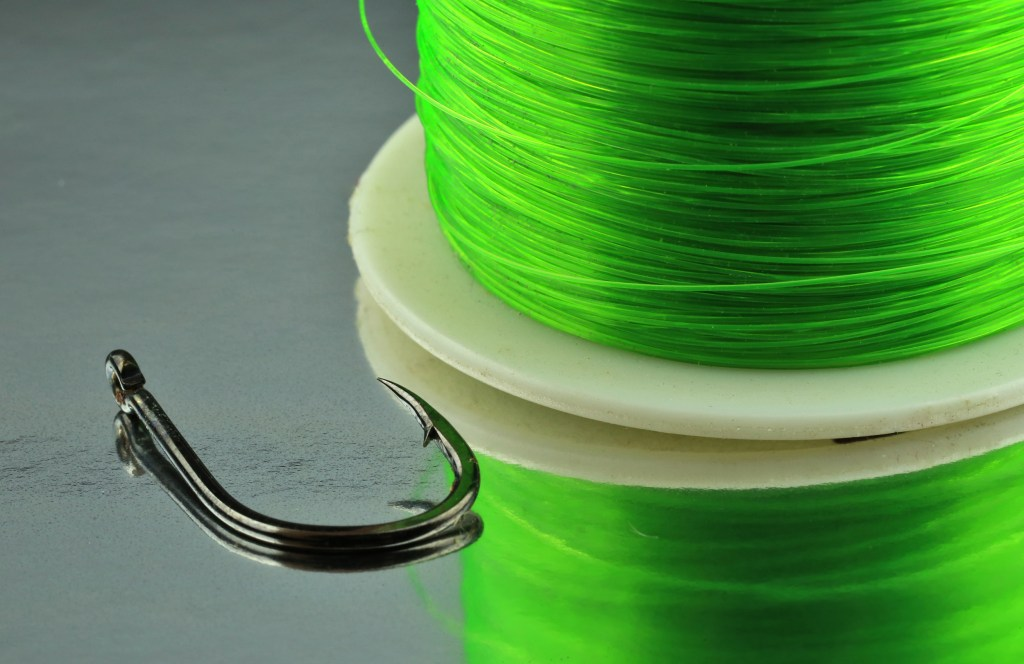 A spool of green copolymer fishing line and a hook on a mirrored surface