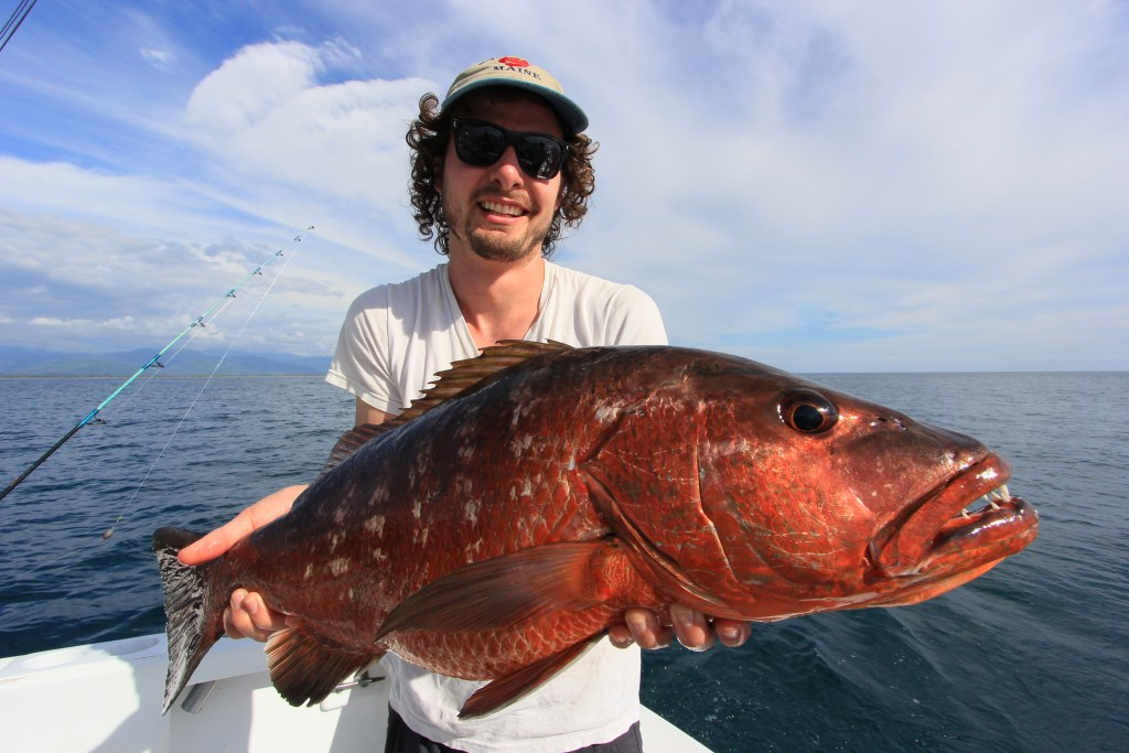A man holding a large Cubera Snapper on a boat, with sea and sky behind him