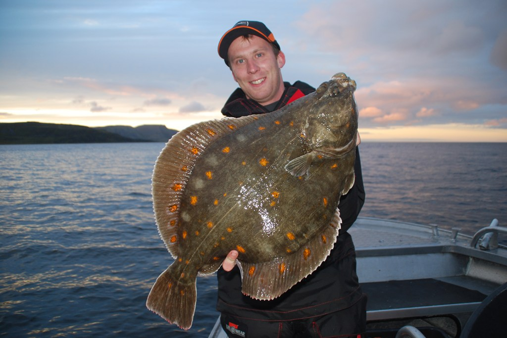 A smiling angler holding a large European Plaice with sea behind him