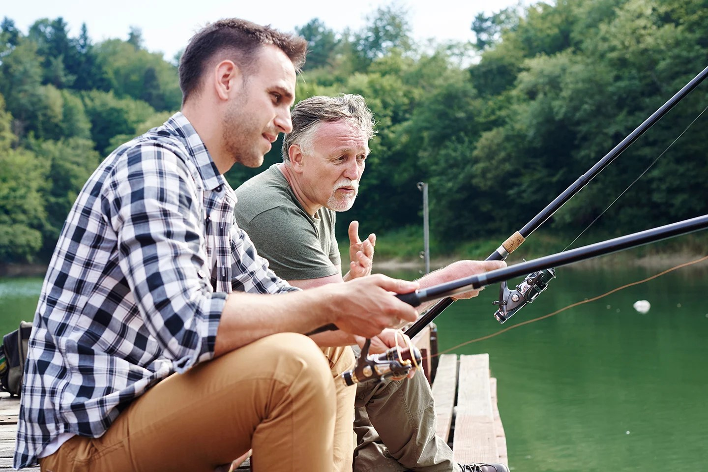Two men talking to each other while fishing on a small jetty