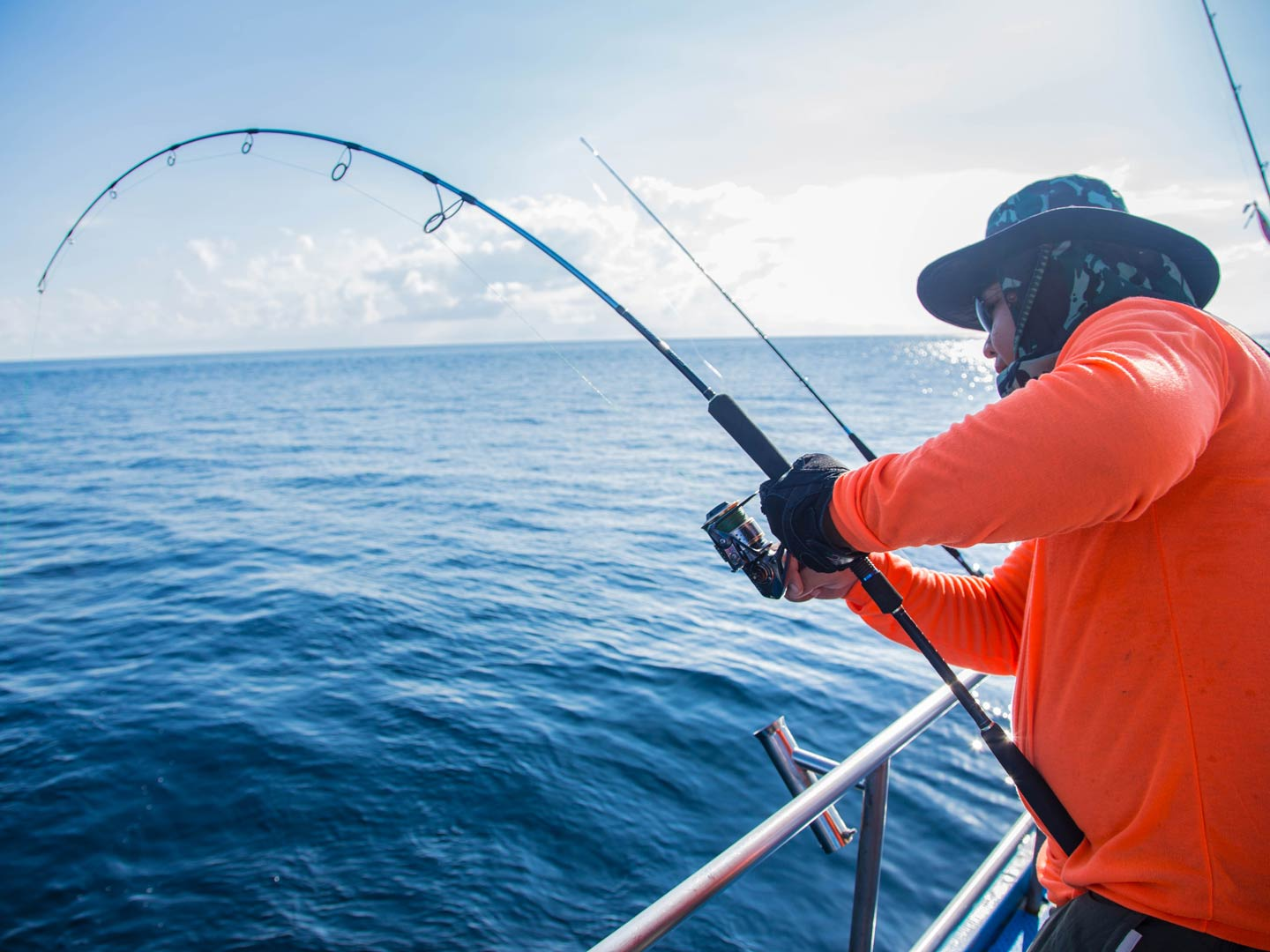 An angler holding on to a bent rod, battling a fish