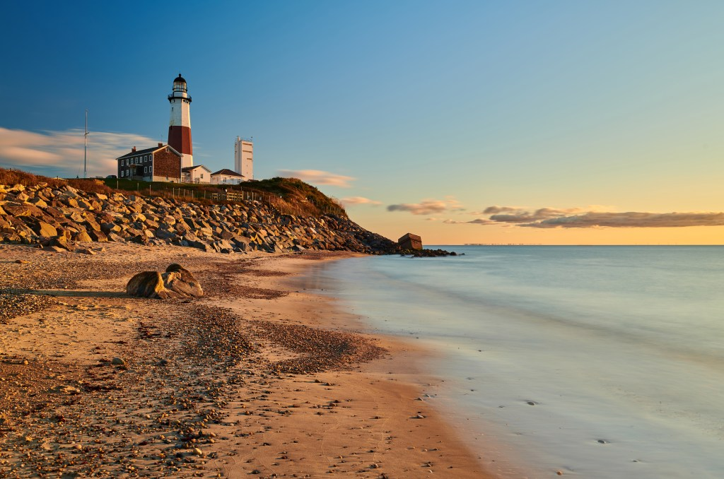 A view along Turtle Cove Beach toward Montauk Lighthouse on Long Island. The sun is rising in the distance.