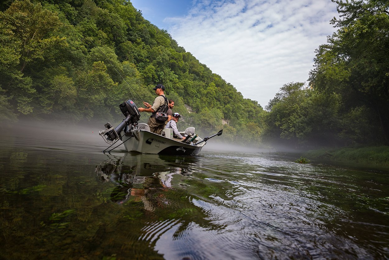 A group of anglers fly fishing together on a drift boat on a river