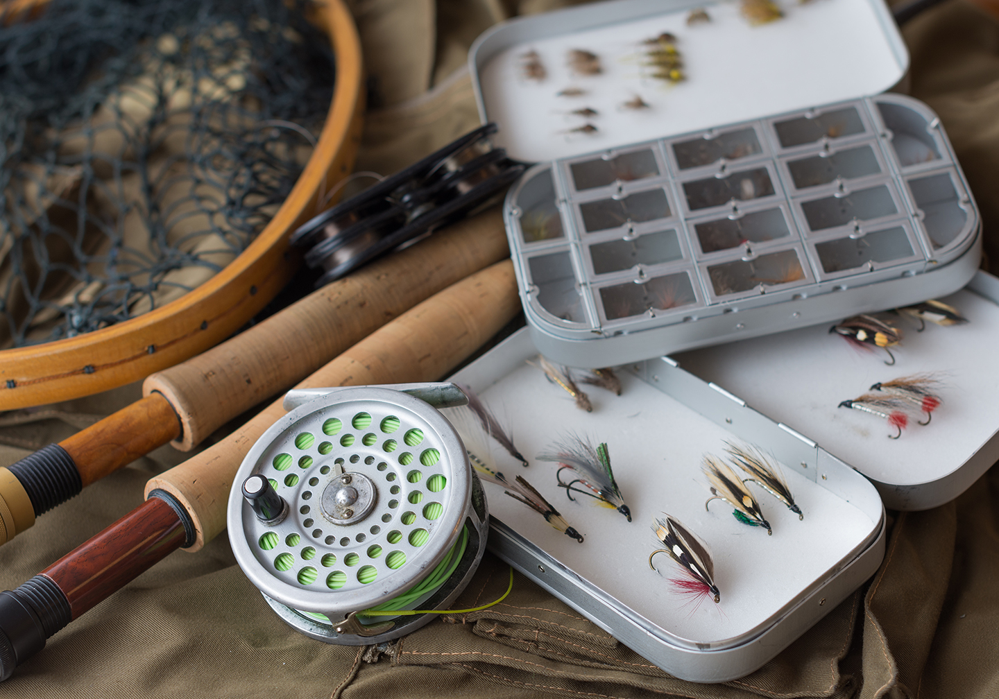 A selection of different fly fishing gear, including a reel, two rods, a net, and a selection of fishing flies.